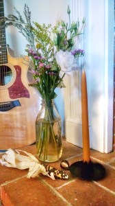 On the hearth of our non-functioning fireplace, some more flowers and a lone candlestick. Guitars always make for good decor.