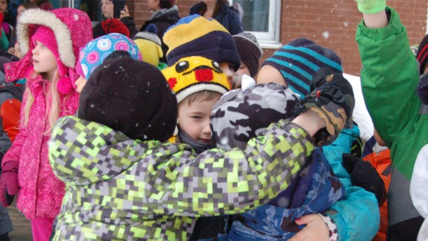 Landon Hayward is hugged by fellow grade one students after riding to school in a fire truck on Mar. 24, 2017.