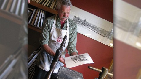 Franc van Oort holds a still damp print from the printing press. Photo credit: Sally Smith.