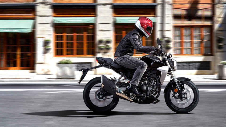 Bočný akčný záber motocykla Honda New Sports Café CB300R pri jazde po ceste.