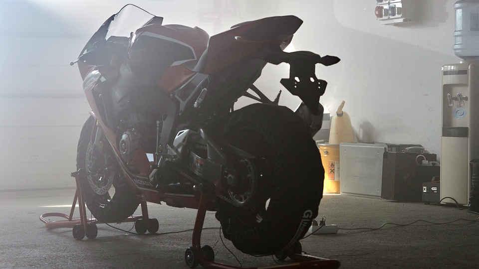 Zadný trojštvrťový pohľad na model Honda CBR1000RR na stojane v dielni.