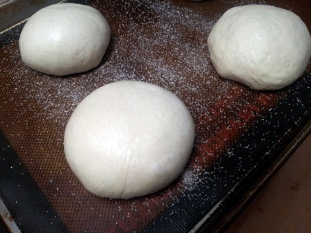 Bread bowls sitting on a baking sheet
