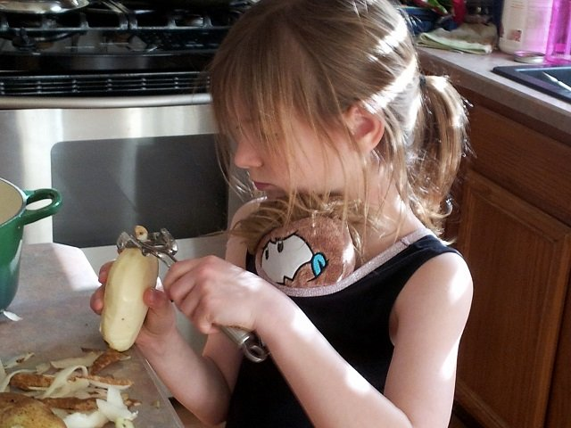 Little Miss peeling potatoes