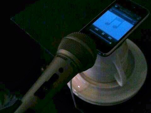 iPhone sitting on a cup with a mic