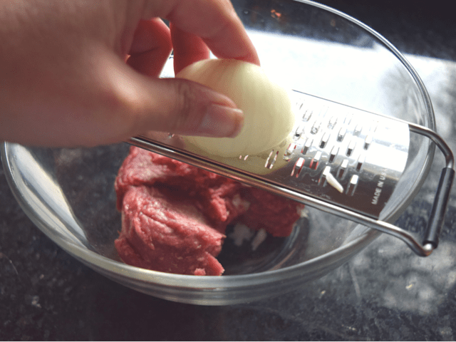 Grating onion into chipotle burgers