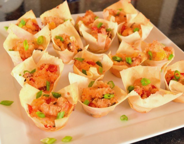 Tomato bacon cups ready to serve with green onion garnish