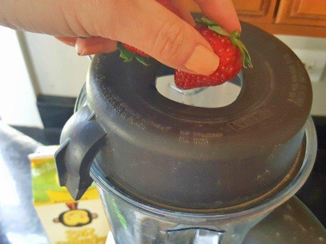 Add frozen strawberries to protein power smoothie bowl