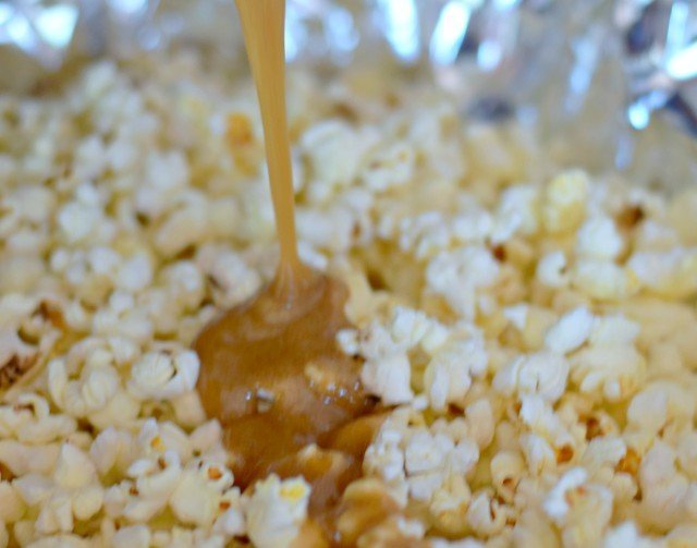 Pour hot caramel onto popcorn