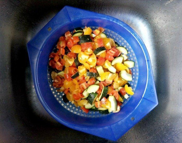 Drain chopped veggies in the sink in a colander