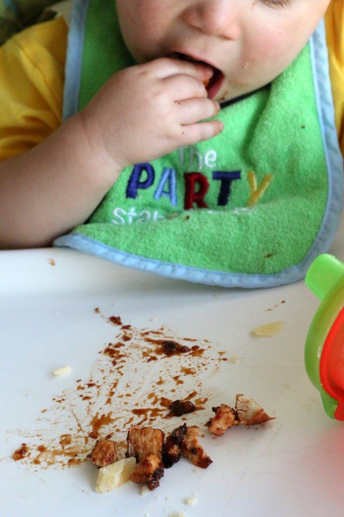 baby eating BBQ chicken