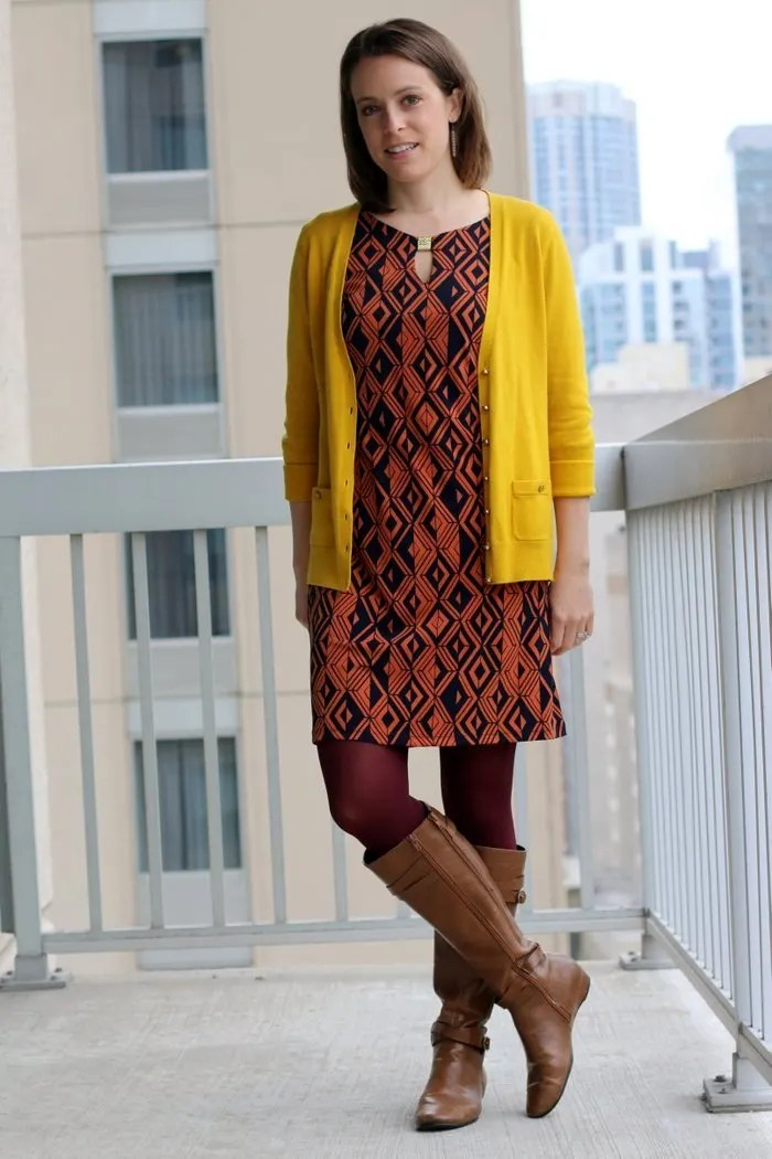 FashionablyEmployed.com | Orange and navy geometric print dress, maroon tights, mustard cardigan and cognac boots | wear to work outfit, office style, workwear