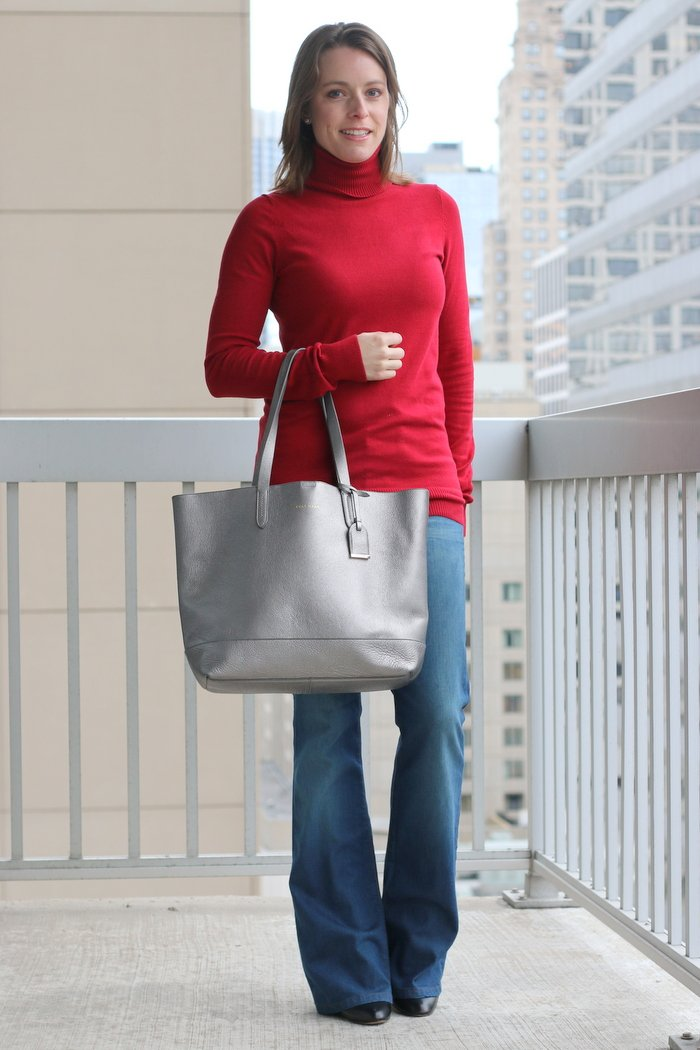 FashionablyEmployed.com | Red sweater with flared jeans and black ankel boots wth a silver bag for winter / subtle holiday style, wear to work, casual Friday | Simple and sustainable style for everyday professional women | wear to work, office style, workwear