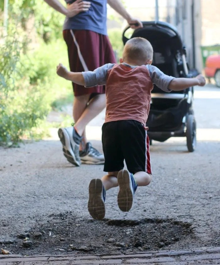 little boy jumping over a pothole in the city
