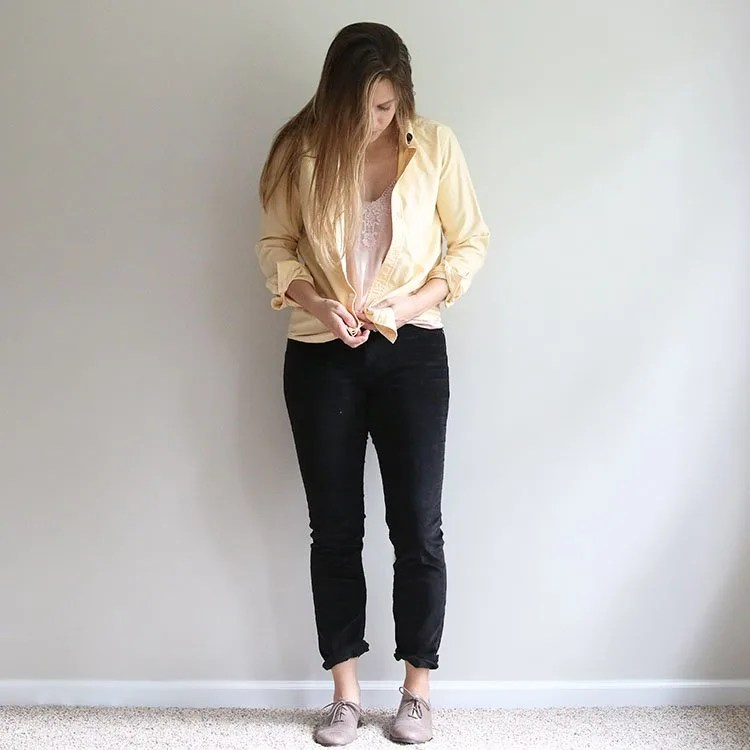 woman tying a knot in a yellow shirt over a pink cami and black corduroy pants