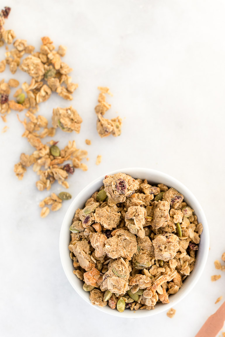 A nut-free pumpkin spice cranberry apple granola full of mega clusters galore!  It's also full of seasonal fall fruits (dried apples and cranberries), pumpkin seeds, and toasted coconut for a healthful balanced snack, breakfast or froyo topping. GF + vegan + sugar free + nut free | Honestly Nourished