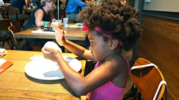 Girl playing with pizza dough at Regents Pizzeria
