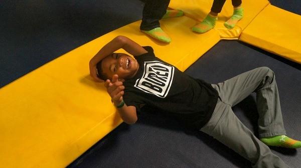 Rockin Jump San Diego, kid laughing, falls down on the trampoline