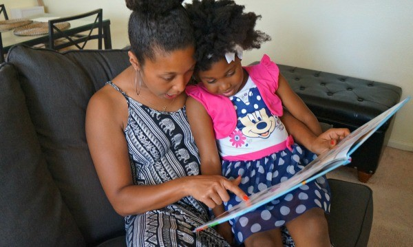 Mother daughter reading together with Disney Jr. Minnie Mouse dress
