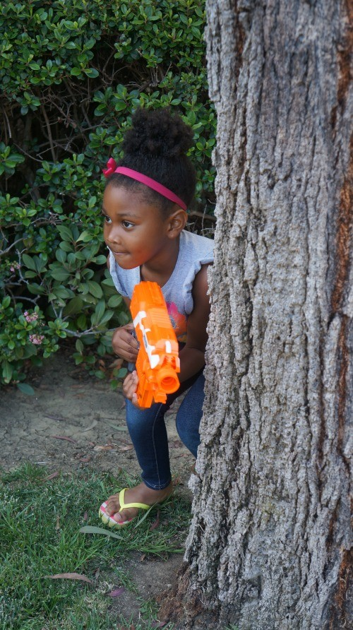 Girl hiding behind a tree in a backyard battle with NERF N-Strike Blasters