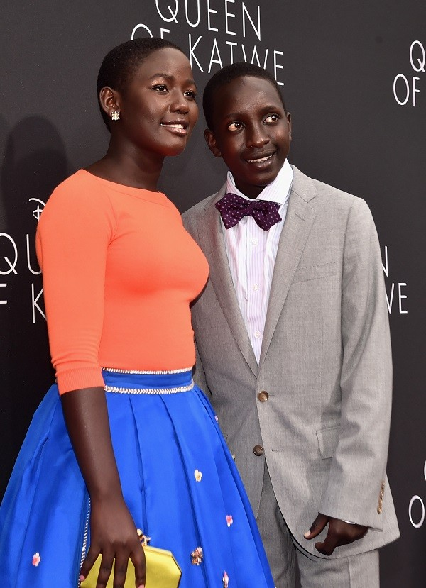 """HOLLYWOOD, CA - SEPTEMBER 20: Actors Madina Nalwanga (L) and Martin Kabanza arrive at the U.S. premiere of Disney's """"Queen of Katwe"""" at the El Capitan Theatre in Hollywood. The film, starring David Oyelowo, Oscar winner Lupita Nyong'o and newcomer Madina Nalwanga, is directed by Mira Nair and opens in U.S. theaters in limited release on September 23, expanding wide September 30, 2016. On September 20, 2016 in Hollywood, California. (Photo by Alberto E. Rodriguez/Getty Images for Disney) *** Local Caption *** Madina Nalwanga; Martin Kabanza"""