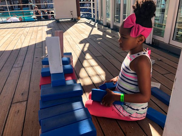 Girl plays with giant block on Carnival Imagination ship
