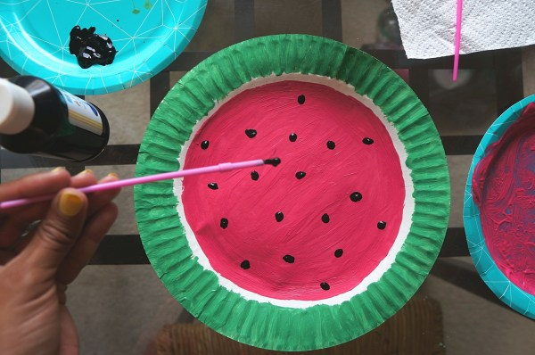 Adding black paint seeds to watermelon paper craft