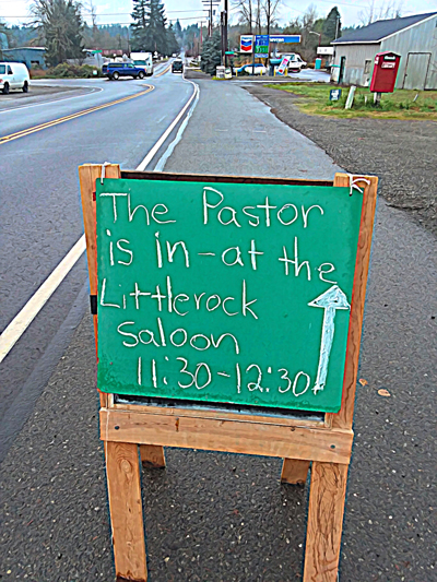 """A sign reading, """"The Pastor is in at the Littlerock Saloon 11:30 to 12:30"""" with an arrow pointing to saloon."""