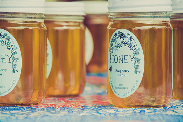 Solid white honey labels with an artistic blue design.