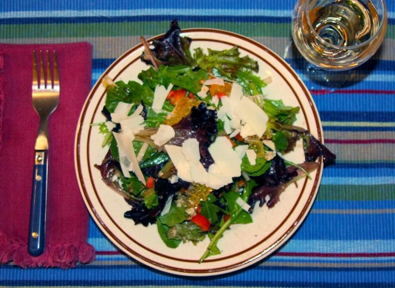 This green salad is topped with chunks of honeycomb and shaved cheese.