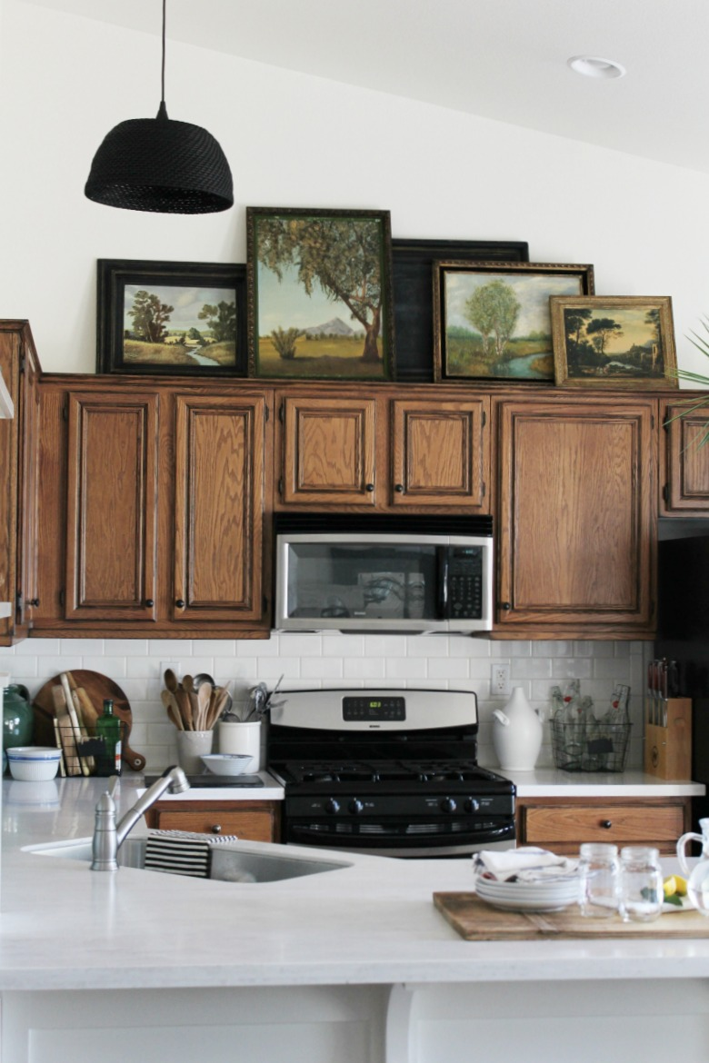 Collection of vintage oil paintings and art above kitchen cabinets