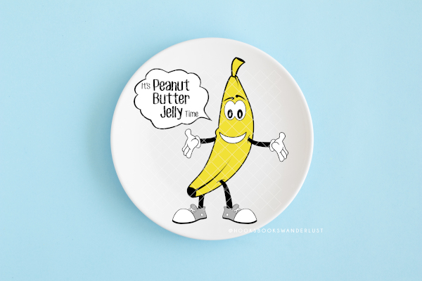 """A white plate sits on a light blue background with a cartoon banana wearing white gloves and grey sneakers shows a speech bubble that reads: """"It's Peanut Butter Jelly Time"""""""