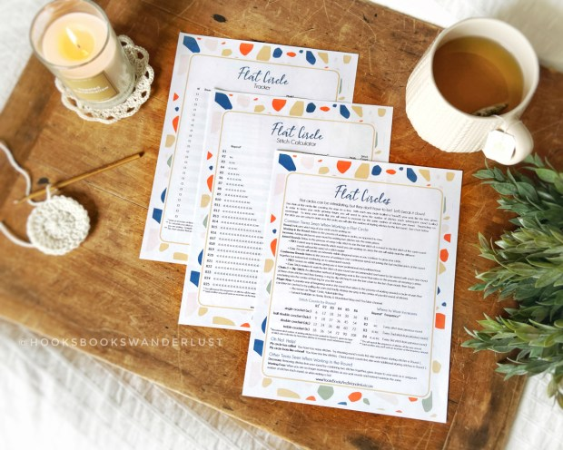 Three staggered Flat Circle cheat sheets are laid out on a wooden background with a partially-crocheted flat circle in cream yarn and bamboo hook, a candle on a cream-colored Marigold Coaster, some greenery off to the side, and a cream colored mug of light colored tea displayed around them