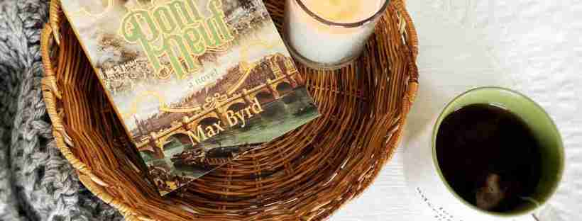 "A light brown, shallow, round wicker basket lays on a white background with a cup of tea, a gray shawl, and a small swatch of gold crochet with a wooden hook arranged around it holds a paperback copy of the title ""Pont Neuf"" by Max Byrd and a white candle."