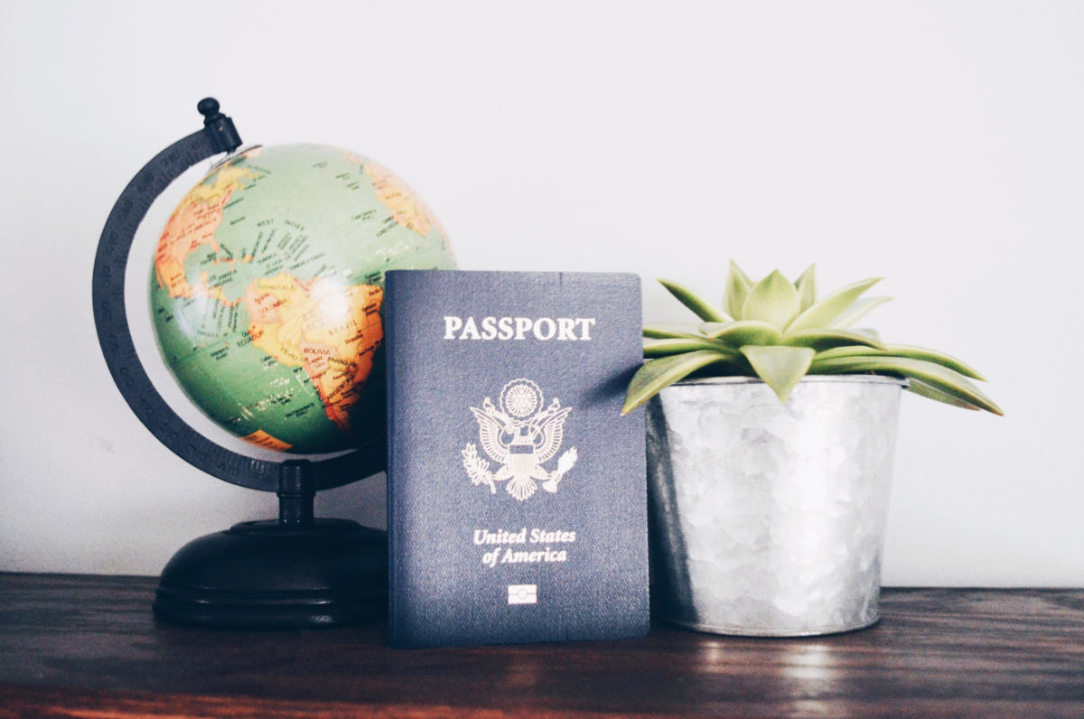 A miniature globe, U.S. Passport and a small succulent in a tin bucket appear grouped on a dark maple mantle.