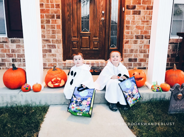 Kristen's two little boys dressed up in handmade ghost costumes sitting on the front porch surrounded by jack-o-lanterns