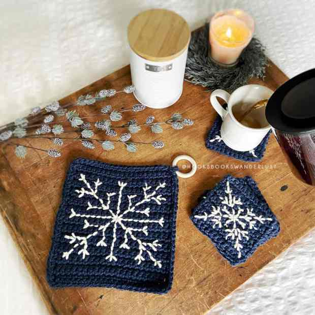A navy blue trivet with a cream embroidered snowflake sits on a wooden board next to a cup of steaming tea being poured and matching navy blue with cream snowflake coasters, surrounded by a fir and pine branches, a white tea cannister, and lit candle.