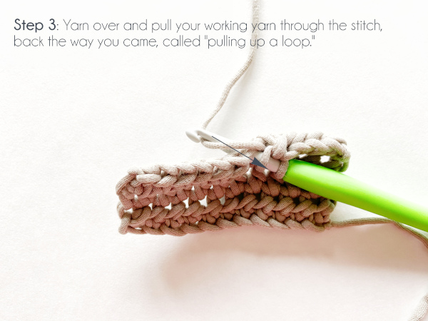 """Step 3: Yarn over and pull your working yarn through the stitch, back the way you came, called 'pulling up a loop.'"" Photo shows a semi-top view of a taupe swatch of half double crochet with a green-handled crochet hook inserted into the stitch where the half double crochet will be worked and the working yarn wrapped over the hook and ready to pull through the stitch in the direction indicated by a blue arrow, which points toward the viewer."
