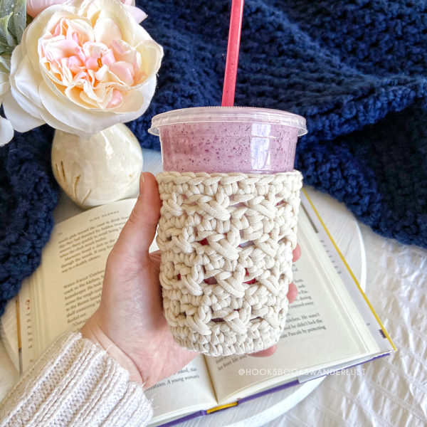 A white XOXO Cold Cup Cozy holds a cup of a purple smoothie in the center of the photo, with an open book and a vase of cream and pastel pink flowers on a white wood tray surrounded by a navy blue throw blanket are in the background.