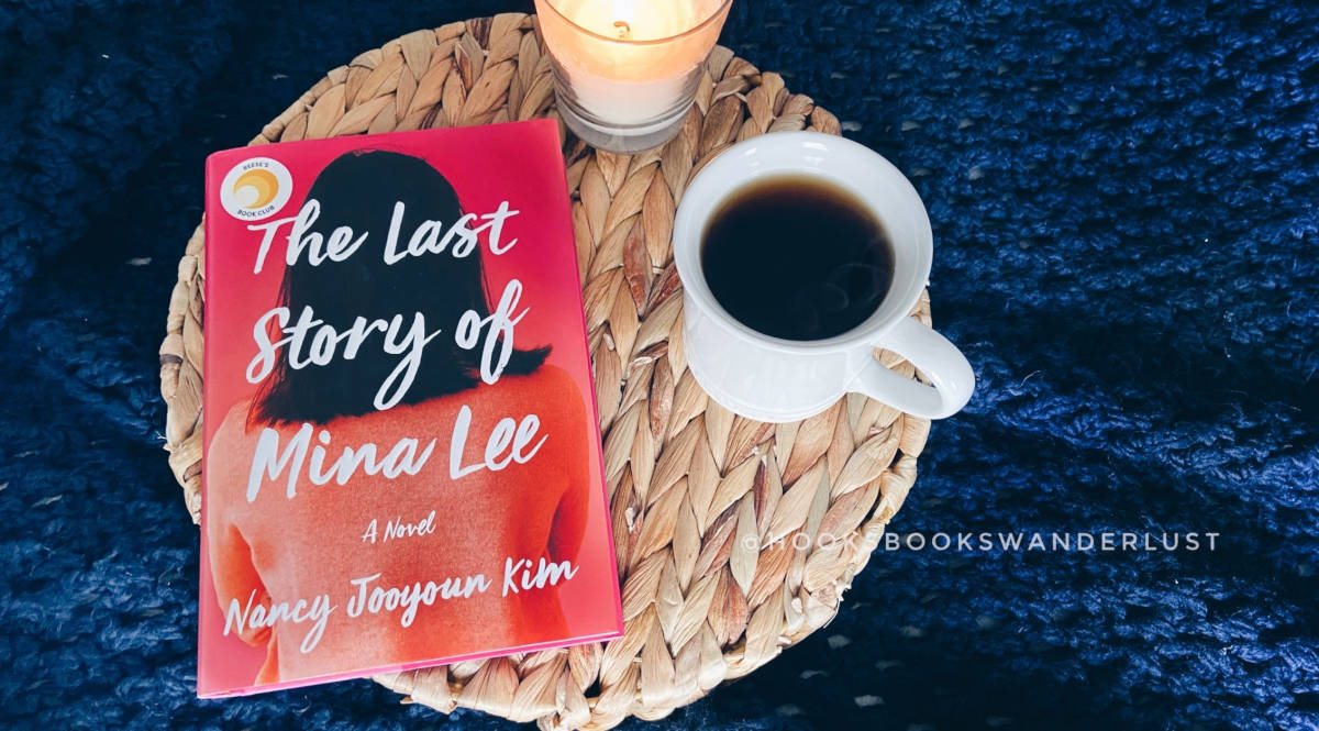 "A hardcover copy of the book titled ""The Last Story of Mina Lee"" by Nancy Jooyoun Kim sits on a wicker tray with a lit cream colored candle and white mug of hot tea with a navy blue crochet blanket in the background."