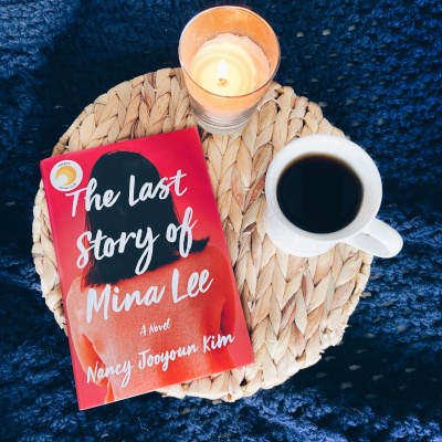 """A hardcover copy of the book titled """"The Last Story of Mina Lee"""" by Nancy Jooyoun Kim sits on a wicker tray with a lit cream colored candle and white mug of hot tea with a navy blue crochet blanket in the background."""