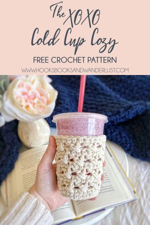 """A white XOXO Cold Cup Cozy holds a cup of a purple smoothie in the center of the photo, with an open book and a vase of cream and pastel pink flowers on a white wood tray surrounded by a navy blue throw blanket are in the background. Text in a light pink box at the top of the photo reads: """"The XOXO Cold Cup Cozy: Free Crochet Pattern. www.hooksbooksandwanderlust.com"""" This image is meant to be saved to a Pinterest board."""