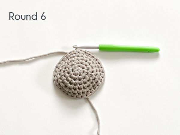 "Six rounds of single crochet have been worked, the first 5 in a flat circle, in a taupe colored cotton yarn laying on a white background. Text on the photo reads: ""Round 6."""