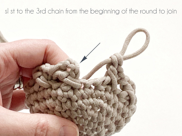 """A half-finished pattern shows the final stitch of Round 7 completed and ready to close the round. An arrow points to the 3rd chain from the chain-4 at the beginning of the round and text at the top of the photo reads: """"sl st to the 3rd chain from the beginning of the round to join."""""""