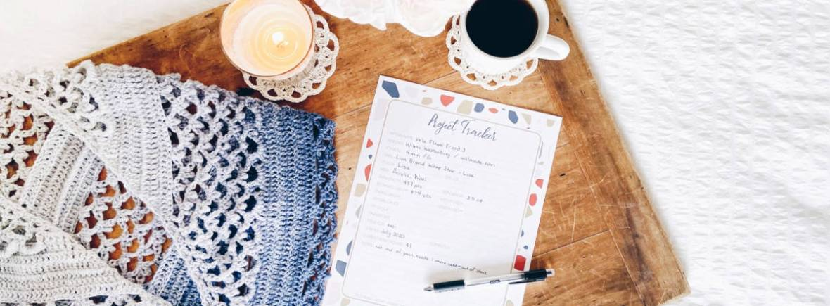 "A lacy shawl in a blue ombre color lays next to a printed piece of paper titled ""Project Tracker,"" a cup of tea and a lit candle sitting on cream colored crochet coasters and a bouquet of flowers in creams, pinks and peach, all on top of a wood board laying on a white background."