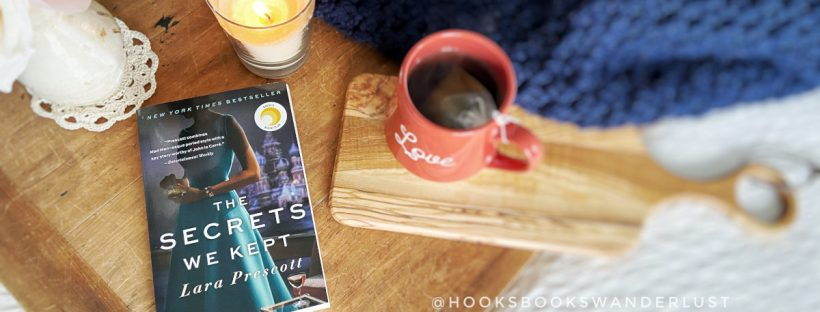 "A paperback copy of the novel ""The Secrets We Kept"" by Lara Prescott sits on a wooden drafting board next to a vase of faux spring blossoms, a lit vanilla candle, and a cup of tea in a burnt orange mug, surrounded by a navy blue throw blanket on top of a white bedspread."