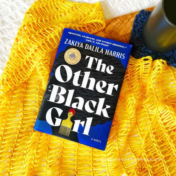 "A hardback copy of the book ""The Other Black Girl"" by Zakiya Dalilia Harris lays on a bright yellow crochet shawl next to a black mug of tea resting on a navy blue crochet coaster."