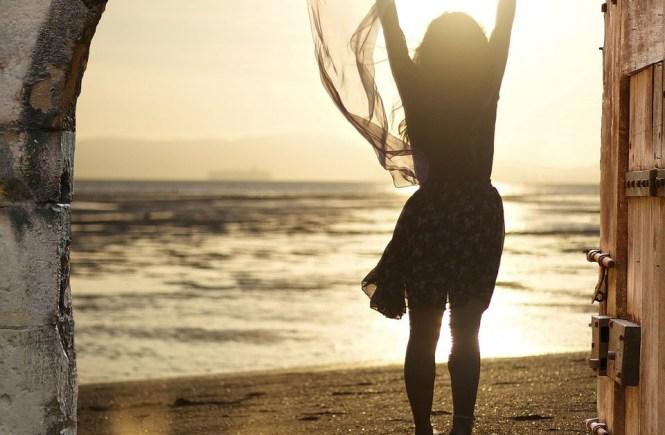 Ein Tor öffnet sich zum Meer mit einer Frau, die befreit ihr Tuch zum Himmel schmeisst - Urlaub im Ich, Hope and shine