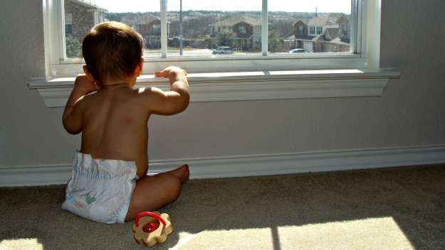 boy wonder looking out his bedroom window