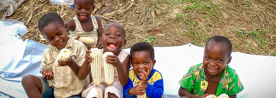 Children with some of the maize harvest