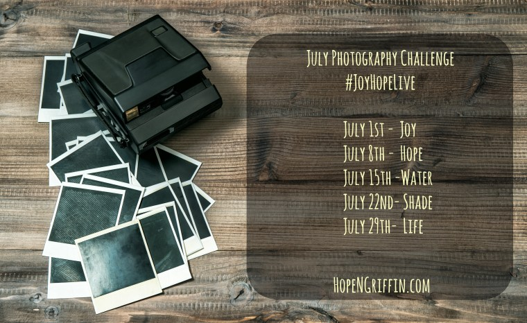 Retro photo camera and frames on rustic wooden background. Vintage style toned picture